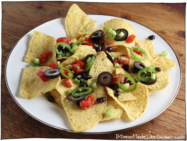 The best damn loaded vegan nachos from here to Timbuktu! Homemade vegan nacho cheese only takes 15 minutes to make, then just load up the tortilla chips will all the best toppings! So easy. #itdoesnttastelikechicken