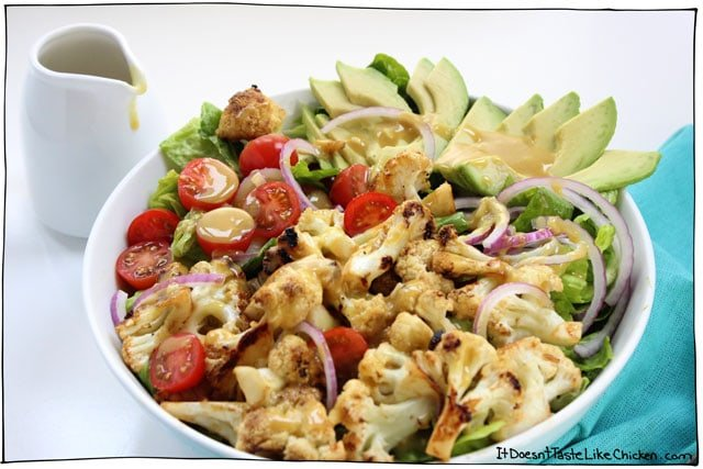 Maple Mustard Cauliflower & Avocado Salad. Sweet mustardy sticky skillet cauliflower florets, on a bed of crispy romaine, with the zing of red onion, pops of cherry tomatoes, and creamy avocado. Salad for dinner or main. Gluten-free. #itdoesnttastelikechicken