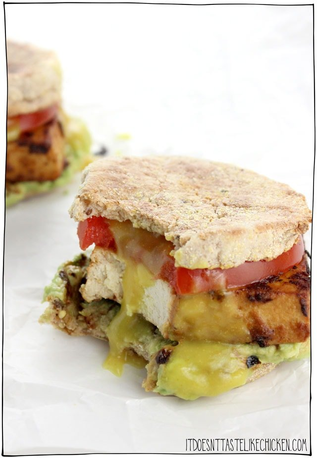 The Ultimate Vegan Breakfast Sandwich! Thick slices of smoky, marinated tofu on an English muffin with mashed avocado, a slice of ripe tomato, and a homemade 5-minute vegan egg yolk inspired sauce. The tofu gets more flavourful the longer it marinates. I just keep it marinating in the fridge, so when morning hunger strikes, it's game on! #itdoesnttastelikechicken #veganrecipes #veganbreakfast #eggfree