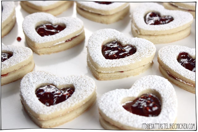 Vegan Linzer Heart Cookies! The buttery soft sugar cookie, sprinkled with powdered sugar, filled with sweet raspberry jam. They are every bit as tasty as they are adorable. Perfect for a gift for a loved one on Valentine's day or other special occasions. Egg-free, dairy-free. #itdoesnttastelikechicken #valentinesday #veganvalentines #veganbaking