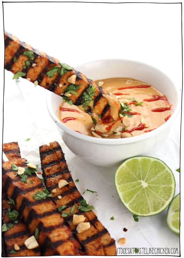 Grilled Tofu Skewers with Spicy Peanut Sauce! The tofu can marinate in the fridge for up to 3 days, then just grill on your BBQ when ready to enjoy. These also work great as a party appetizer. #itdoesnttastelikechicken #veganrecipes #veganbbq #tofurecipe