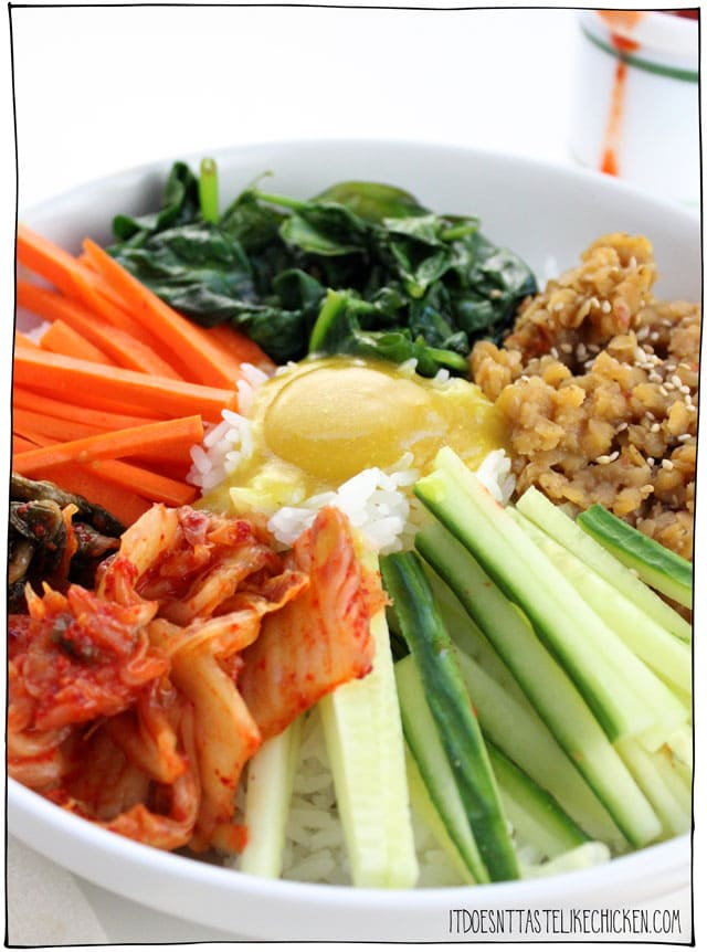 Vegan Korean Bibimbap with a vegan egg yolk! This Korean inspired vegan bibimbap is full of flavour with sweet and savoury lentils, sautéed spinach, kimchi, fresh carrots and cucumbers, and a rich and easy to make vegan egg yolk sauce. #itdoesnttastelikechicken #bibimbap #veganrecipes #koreanrecipe