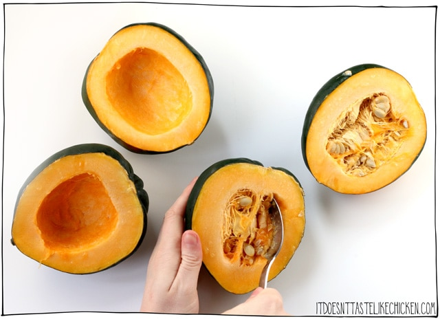 Prepare the acorn squash for stuffing by halving them and scooping out the guts and seeds.
