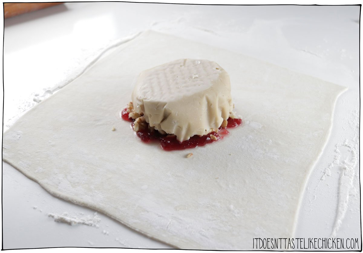 Spread the cranberry sauce in the middle, sprinkle with walnuts, and top with the frozen vegan brie.