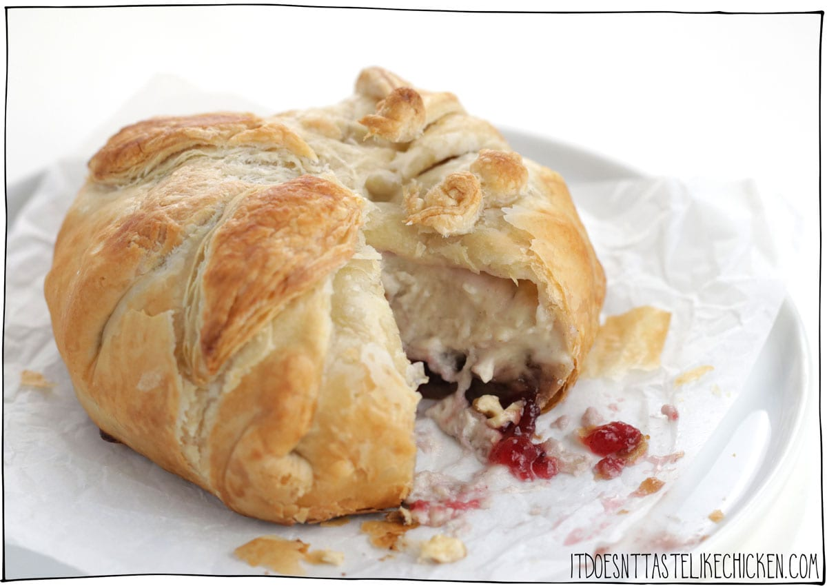 This Vegan Baked Brie in Puff Pastry is the stuff of holiday appetizer dreams!!!! Gooey homemade easy-to-make vegan brie cheese is paired with cranberry sauce, walnuts, and wrapped up in flaky crispy puff pastry. Don't be surprised when this gets gobbled up at lightning speed. The perfect appetizer for Christmas, Thanksgiving, or any holiday party. #itdoesnttastelikechicken #veganappetizer #veganchristmas #vegancheese