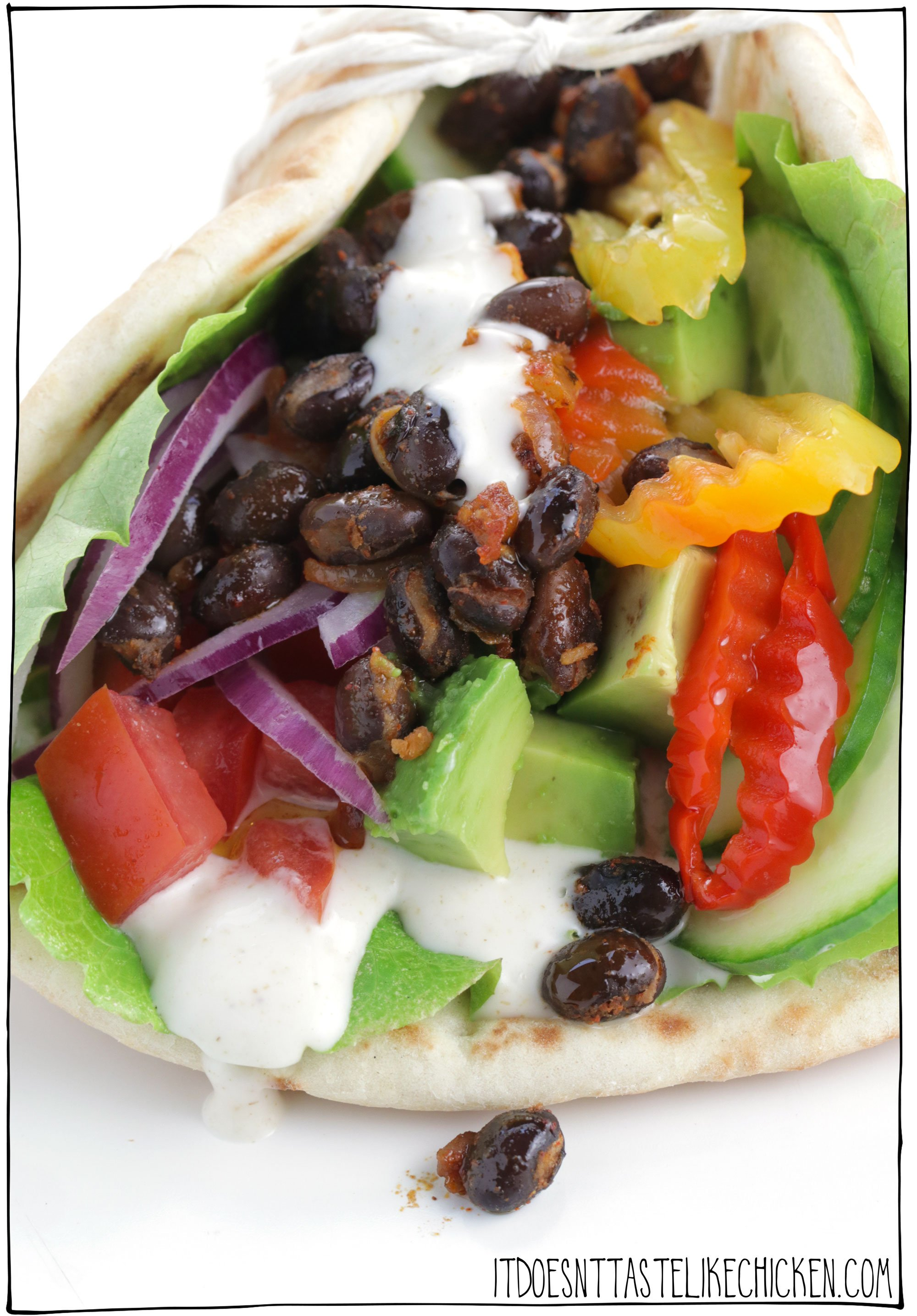Vegan Spicy Black Bean Pita Sandwich! This 20-minute vegan pita is next-level delicious! With spicy black beans, a creamy tangy mayo, and a mountain of fresh veg, this is the perfect hearty vegan sandwich the enjoy for lunch or dinner. These sandwiches can be made oil-free, gluten-free, and if you don't have any pitas on hand, feel free to load all of these toppings into a wrap or on your favourite sandwich bread. #itdoesnttastelikechicken #veganrecipes